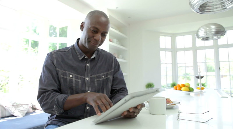 stock-footage-african-american-man-working-on-digital-tablet-at-kitchen-counter-whilst-drinking-cup-of-coffee