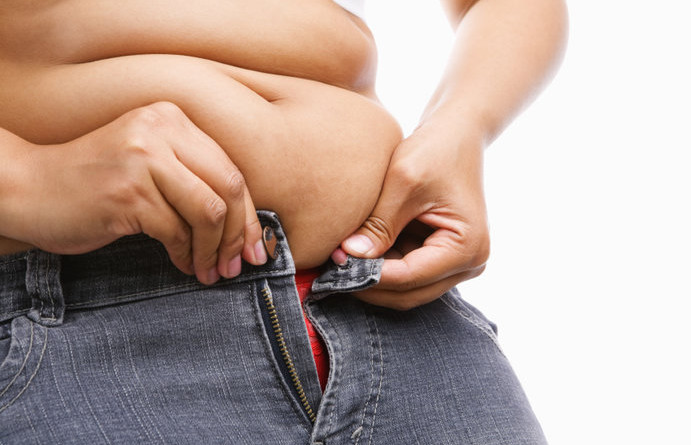 Woman trying hand to zipper her jeans, a concept for obesity issue